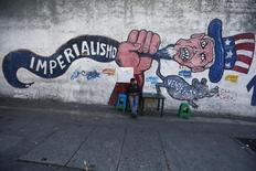 """Человек сидит у стены с граффити в Каракасе 9 марта 2015 года. США пытаются заблокировать соглашение между странами ОПЕК и вне картеля, призванное помешать снижению цен на нефть, сказал президент Венесуэлы Николас Мадуро во вторник, обвинив Вашингтон в оказании """"военного"""" давления для предотвращения заключения сделки. REUTERS/Jorge Silva"""