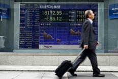 Мужчина проходит мимо экрана с котировками индекса Nikkei average в Токио 1 апреля 2016 года. Японские акции завершили торги пятницы на отрицательной территории, так как инвесторы зафиксировали прибыль после трёхдневного ралли.  REUTERS/Thomas Peter