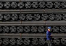 Imagen de archivo de un trabajador pasando junto a tubos de acero en la planta Youfa de Tangshan, en la provincia china de Hebei. 3 noviembre 2015. El acuerdo de China para eliminar el subsidio a la exportación de algunos productos de aluminio y acero podría inundar al saturado mercado global, mientras los productores luchan por vender el exceso de metal antes de que ocurran los cambios, agudizando los problemas de la industria, dijeron operadores. REUTERS/Kim Kyung-Hoon