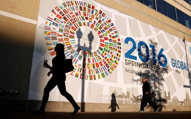 A woman walks past the International Monetary Fund headquarters during the IMF and World Bank Spring Meetings in Washington April15, 2016.REUTERS/Kevin Lamarque