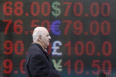 Прохожий у пункта обмена валюты в Москве. 18 апреля 2016 года. Рубль был в минусе на торгах понедельника, отражая падение нефтяных котировок после неудачных переговоров крупнейших стран-производителей о заморозке добычи, однако отсутствие драматических изменений на мировом рынке нефти и заметные продажи экспортной выручки на локальном валютном рынке удержали российскую валюту от обвала. REUTERS/Sergei Karpukhin