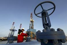 Рабочи проверяет вентиль на нефтепроводе на месторождении Имилорское.  Фьючерсы на нефть торгуются в минусе в среду, поскольку инвесторы вновь начали тревожиться относительно переизбытка предложения на мировых рынках после окончания трёхдневной забастовки рабочих нефтегазовой отрасли Кувейта. REUTERS/Sergei Karpukhin/File Photo