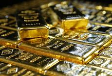 Слитки золота на заводе 'Oegussa' в Вене. 18 марта 2016 года. Золото немного подешевело в пятницу на фоне усиления доллара к иене, но все еще собирается завершить неделю в плюсе, а серебро настроено на самый большой недельный прирост за 11 месяцев. REUTERS/Leonhard Foeger