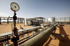 Нефтяное месторождение Эш-Шарара в Ливии. 3 декабря 2014 года. Цены на нефть выросли более чем на 2 процента в пятницу и могут завершить подъёмом третью неделю кряду за счёт улучшения рыночных настроений на фоне признаков, что переизбыток предложения на мировых рынках может уменьшаться. REUTERS/Ismail Zitouny/File Photo