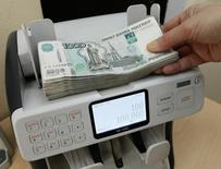 Кассир пересчитывает 1000-рублевые купюры. Рубль ушел в минус после позитивного открытия биржевых торгов на фоне попыток нефтяных котировок сократить утренние потери, пока неудачных, а также в последний день уплаты НДПИ, для которого, по оценке участников рынка, основные потоки экспортной выручки могли пройти заранее, а сегодня ожидаются лишь точечные продажи.  REUTERS/Ilya Naymushin
