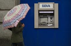 BBVA, el segundo mayor banco español, anunció el jueves unos resultados inferiores a lo previsto que propiciaron una caída de casi un ocho por ciento en el precio de la acción. En la imagen, una mujer con paraguas junto a un cajero de BBVA en Madrid, el 4 de abril de 2016. REUTERS/Andrea Comas