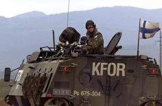 Финский солдат на крыше бронетранспортера в районе македонской столицы Скопье 29 марта 2001 года. Финляндия выбирает между членством НАТО и отношениями с Россией. Reuters Photographer