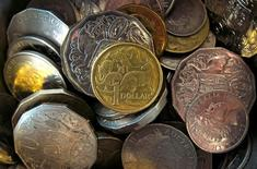 El banco central de Australia recortó el martes los tipos de interés a un mínimo histórico de un 1,75 por ciento, la primera flexibilización de su política monetaria en un año, en momentos en que busca frenar un repunte de su moneda y aislar a la economía de una posible deflación En la imagen, un dólar australiano entre varias monedas del país en una tienda de Sídney, el 11 de febrero de 2016. REUTERS/David Gray