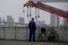 A worker stands on a dock next to the Huangpu river in Shanghai, November 25, 2014.  REUTERS/Aly Song