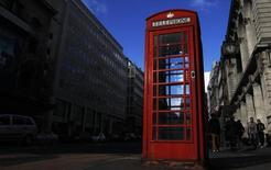 A traditional public red phonebox is illuminated by the sun in London February  19, 2012.   REUTERS/Luke MacGregor