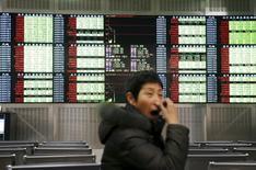 Инвестор на фоне табло с биржевой информацией в Шанхае 7 января 2016 года. Фондовый рынок Китая завершил торги среды практически без изменений на фоне приближения Шанхайского индекса к техническому уровню сопротивления, а также признаков ослабления производственной активности. REUTERS/China Daily