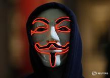 Сторонник группы хакеров Anonymous в маске Гая Фокса в ходе акции протеста в Лондоне 5 ноября 2015 года. Греческий Центробанк во вторник подвергся кибератаке группы хакеров Anonymous, приведшей к сбою в работе сайта регулятора, сообщил представитель Банка Греции в среду. REUTERS/Peter Nicholls