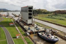 Tugboats help a barge through the Miraflores locks as it transports the last rolling gate for new locks on the  Panama Canal, in Panama City December 10, 2014. REUTERS/Rafael Ibarra