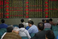 Inversores miran una pantalla electrónica que muestra información bursátil, en una correduría en Shanghái, China. 21 de abril de 2016. Las acciones chinas subieron levemente el jueves, pero el volumen de transacciones permaneció cerca de mínimos en cuatro meses en medio de nuevas señales de que la incipiente recuperación económica del país descansa sobre cimientos débiles. REUTERS/Aly Song