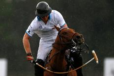 Britain's Prince Harry plays polo in the rain during the Sentebale Royal Salute Polo Cup in Wellington, Florida, U.S., May 4, 2016. REUTERS/Carlo Allegri.