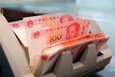 Банкнты достоинством 100 юаней в счетной машине в отделении банка в Пекине. Банк России привлек в прошлом году у Народного банка Китая 10 миллионов китайских юаней (112 миллионов рублей) в рамках соглашения о свопе в национальных валютах, говорится в годовом отчете российского регулятора.  REUTERS/Kim Kyung-Hoon
