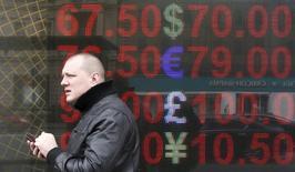 Мужчина стоит рядом с табло с курсами обмена валют в Москве. Центробанк РФ в марте зафиксировал рост чистого спроса населения на наличную иностранную валюту по сравнению с февралем, сообщил регулятор на своем сайте, объяснив это снижением курса доллара и евро к рублю.  REUTERS/Sergei Karpukhin