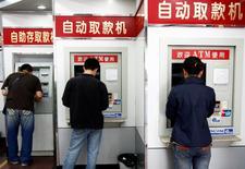 """Imagen de archivo de unas personas utilizando cajeros automáticos en Shenyang, China, mayo 19, 2007. China podría sufrir una crisis financiera y una recesión económica si el Gobierno depende demasiado del estímulo impulsado por la deuda, dijo una """"persona acreditada"""" citada el lunes por el diario oficial People's Daily.  REUTERS/Stringer"""