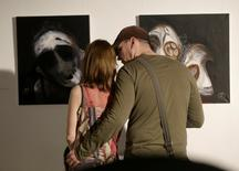 People look at paintings by Syrian artist Majd Kara, who fled his country, in Vilnius, Lithuania, May 5, 2016. REUTERS/Ints Kalnins