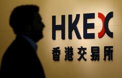 Человек идет мимо входа в Гонконгскую фондовую биржу. Китайский фондовый рынок завершил торги четверга в плюсе, восстановив первоначальные потери, поскольку объявленный Пекином план инвестиций в транспортные проекты в объеме $724 миллиардов подтолкнул акции инфраструктурных компаний вверх и ослабил опасения по поводу возможных изменений экономической политики государства.   REUTERS/Bobby Yip/File Photo