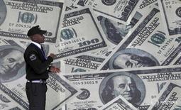 Охранник проходит мимо стены с изображениями долларовых банкнот в столице Кении Найроби 23 июля 2015 года. Доллар удерживает некоторое преимущество к иене и евро в пятницу накануне выхода данных, способных повлиять на динамику американской валюты.  REUTERS/Thomas Mukoya/File Photo