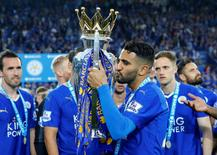Britain Soccer Football - Leicester City v Everton - Barclays Premier League - King Power Stadium - 7/5/16 Leicester City's Riyad Mahrez kisses the trophy as he celebrates winning the premier league Reuters / Darren Staples Livepic