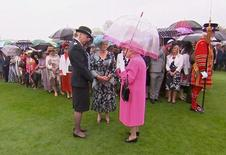 Britain's Queen Elizabeth speaks to Commander Lucy D'Orsi during a garden party at Buckingham Palace in London, in this still image taken from video, Britain, May 10, 2016. REUTERS/ROYAL POOL via Reuters TV