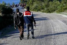 Турецкий жандарм ведет человека, подозреваемого в контрабанде нелегальных мигрантов, в городе Дикили 5 марта 2016 года. Контрабандисты, перевозящие нелегальных мигрантов, заработали свыше $5 миллиардов благодаря транспортировке людей на юг Европы в прошлом году, говорится в совместном докладе Интерпола и Европола, опубликованном во вторник. REUTERS/Umit Bektas/File photo