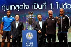 Football club Leicester City captain (L-R) Wes Morgan, vice chairman Vichai Srivaddhanaprabha, owner Vichai Srivaddhanaprabha, manager Claudio Ranieri and player Kasper Schmeichel stand on stage next to the club's English Premier League trophy during a meeting with the media in Bangkok, Thailand May 18, 2016. REUTERS/Jorge Silva