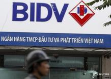 Человек проходит мимо отделения Банка инвестиций и развития Вьетнама (BIDV) в Ханое 8 января 2016 года. ЦБР аккредитовал представительство в Москве Банка инвестиций и развития Вьетнама (BIDV), сообщил регулятор в четверг. Nguyen Huy Kham / Reuters
