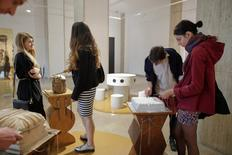 """Visitors interact with pieces of wood, marble and metal during an art exhibition titled """"The Meekness of the World. This is not a stone"""" that aims to familiarize Romanians with the work of modernist giant Constantin Brancusi, in Bucharest, Romania, May 19, 2016.  Inquam Photos/Octav Ganea/via REUTERS"""