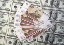 Рублевые и долларовые купюры в Сараево 9 марта 2015 года. Рубль торгуется в минусе на сессии понедельника, но его отрицательная динамика в ответ на дешевеющую нефть компенсируется продажей экспортной выручки под уплату в среду НДПИ. REUTERS/Dado Ruvic