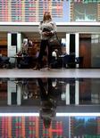 Una mujer observando un panel electrónico en la Bolsa de Valores de Sao Paulo, Mayo 9, 2016. El tono negativo se imponía el lunes por la mañana en la bolsa de Brasil, ante el impacto causado por la divulgación de unos diálogos donde el ministro de Planificación sugiere detener el avance de una extensa investigación sobre corrupción centrada en la compañía brasileña Petrobras.  REUTERS/Paulo Whitaker