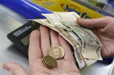 """Продавец в магазине пересчитывает рубли. Рубль в минусе вечером пятницы на фоне снижения нефти и умеренного роста доллара на форексе, но негативная динамика в течение дня сдерживалась остаточными продажами валютной выручки под уплату налога на прибыль в понедельник, в который расчеты """"сегодня"""" по доллару не будут производиться из-за выходного в США. REUTERS/Ilya Naymushin"""