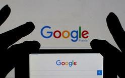 """Francia """"llegará hasta el final"""" para asegurarse de que las multinacionales que operan en su territorio pagan sus impuestos y podrían conocerse nuevos casos después de que Google y McDonald's fuesen objeto de registros fiscales, dijo el ministro de Finanzas francés, Michel Sapin.  En la imagen, una mujer sostiene su teléfono inteligente, que muestra la página de inicio de Google. Ilustración fotográfica realizada el 24 de febrero de 2016. REUTERS/Eric Gaillard/Illustration"""