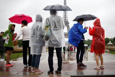 Tourists stroll on the Trocadero square, in front of the Eiffel Tower during a rainy day in Paris, France, May 30, 2016.   REUTERS/Charles Platiau