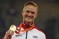 Greg Rutherford of Britain presents his gold medal as he poses on the podium after the men's long jump event during the 15th IAAF World Championships at the National Stadium in Beijing, China, August 26, 2015.          REUTERS/Damir Sagolj