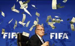 Notas de dinheiro falso em volta do ex-presidente da Fifa Joseph Blatter, lançadas por um manifestante. REUTERS/Arnd Wiegmann