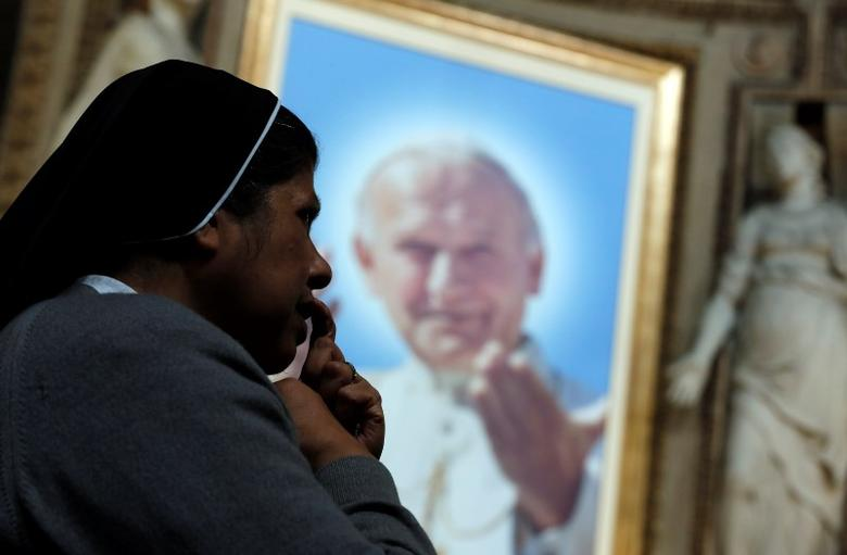 A nun prays in front of a painting depicting Pope John Paul II inside St. Sprit in Sassia church in Rome, April 24, 2014. REUTERS/Yara Nardi
