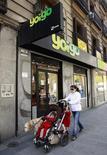 Goldman Sachs ha acordado asegurar la financiación la oferta de Zegona si el grupo inversor británico consigue llegar a un acuerdo para adquirir el operador móvil Yoigo, dijo una fuente cercana a la operación. En la imagen de archivo, una mujer y dos niños pasan junto a una tienda de Yoigo en Madrid, el 26 de abril de 2011. REUTERS/Andrea Comas