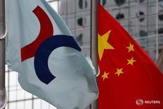 Флаг с логотипом Гонконгской биржи (слева) и флаг КНР в Гонконге 7 июня 2016 года. Китайский фондовый рынок завершил торги вторника почти без изменений вопреки росту в Гонконге и на других азиатских площадках, которому способствовало ослабление ожиданий скорого повышения процентных ставок в США. REUTERS/Bobby Yip