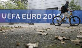 A man walks with his bicycle past a banner reading 'UEFA EURO 2016' at the Euro 2016 International Broadcast Center in Paris, France June 6, 2016.  REUTERS/Gonzalo Fuentes