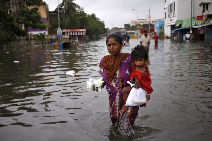 A woman carries her child and milk packets as she wades through a flooded street in Chennai, India, December 5, 2015. REUTERS/Anindito Mukherjee/File Photo