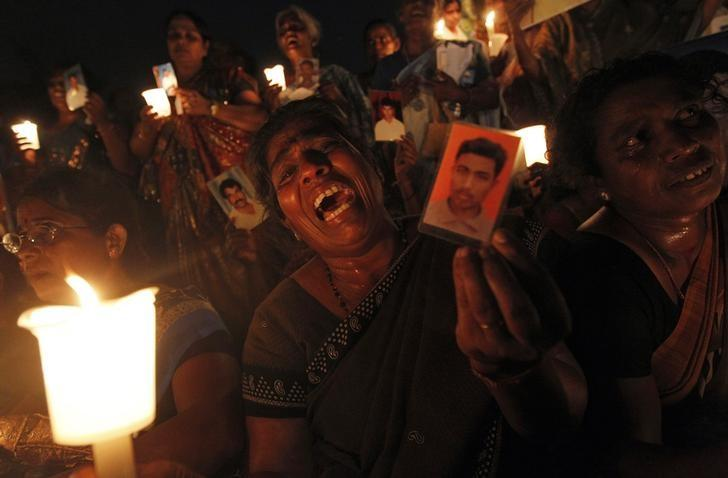 A Tamil woman cries as she holds up an image of her family member who disappeared during the civil war with the Liberation Tigers of Tamil Eelam (LTTE) at a vigil to commemorate the international day of the disappeared in Colombo August 30, 2013.  REUTERS/Dinuka Liyanawatte/File Photo