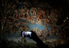 A visitor takes pictures with his cellphone at a full-size replica of the Sistine Chapel after the opening ceremony in Mexico City, Mexico June 7, 2016. REUTERS/Henry Romero