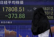Un peatón que se cubre de la lluvia camina junto a un tablero electrónico que muestra información bursátil, en una correduría afuera de Tokio, Japón. 4 de septiembre de 2015. Las bolsas de Asia caían el viernes mientras los inversores buscaban refugio en los activos seguros, por la inquietud sobre el referendo del 23 de junio que podría llevar a la salida del Reino Unido de la Unión Europea. REUTERS/Yuya Shino