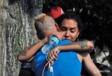 Friends and family members embrace outside the Orlando Police Headquarters during the investigation of a shooting at the Pulse nightclub, where people were killed by a gunman, in Orlando, Florida, U.S June 12, 2016.  REUTERS/Steve Nesius - RTX2FR9H