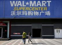 Pedestrians walk past a signboard of Wal-Mart at its branch store in Beijing, China, October 15, 2015.  REUTERS/Kim Kyung-Hoon