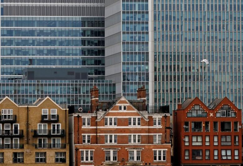 Apartment buildings are backdropped by skyscrapers of banks at Canary Wharf in London, Britain October 30, 2015. REUTERS/Reinhard Krause/File Photo