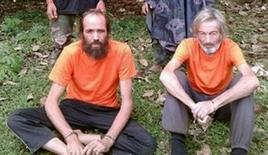 Hostages Canadian national Robert Hall (R) and Norwegian national Kjartan Sekkingstad (L) are seen in this undated picture released to local media, in Jolo island in southern Philippines. The Philippines confirmed on Tuesday the execution of Robert Hall, a Canadian who had been held hostage by the al Qaeda-linked Abu Sayyaf Islamist militant group on a remote southern island with three other people since September 2015. Handout/ via REUTERS